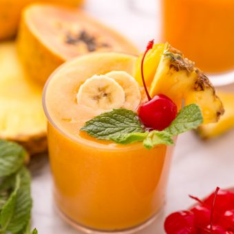 This refreshing tropical smoothie recipe is made with exotic fruit like mango, pineapple, and papaya! Ready in less than 5 minutes, this delicious and healthy treat is the perfect way to start your morning! Makes 2 smoothies, but can easily be double or tripled as needed!#tropicalsmoothie #fruitsmoothie #smoothies #smoothie #pineapplesmoothie #tropical