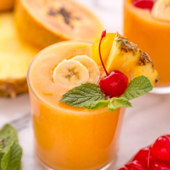This refreshing tropical smoothie recipe is made with exotic fruit like mango, pineapple, and papaya! Ready in less than 5 minutes, this delicious and healthy treat is the perfect way to start your morning! Makes 2 smoothies, but can easily be double or tripled as needed! #tropicalsmoothie #fruitsmoothie #smoothies #smoothie #pineapplesmoothie #tropical