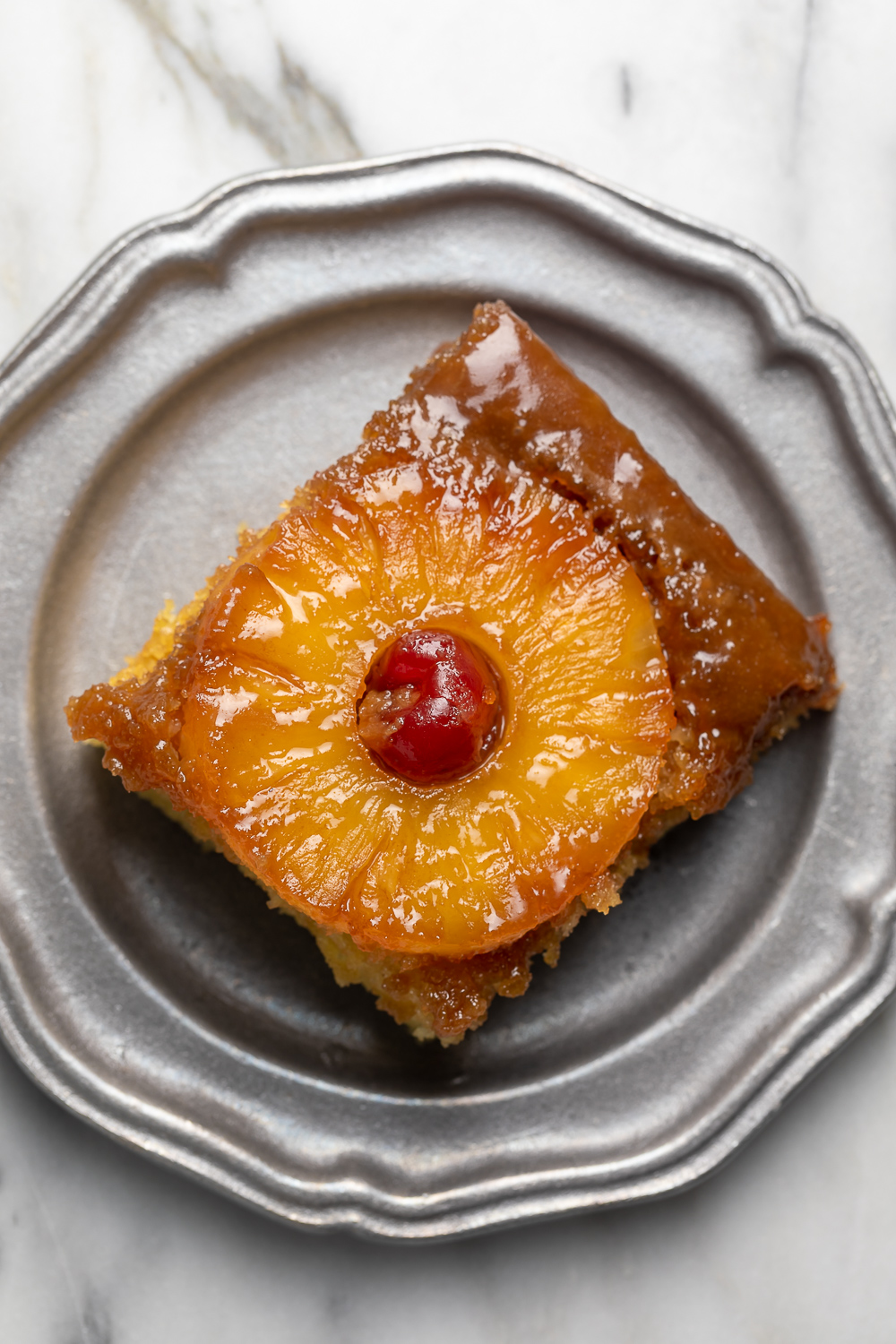 Pineapple Upside-Down Cake is sticky, sweet, and so delicious! This version serves a crowd and is easy enough to whip up on a weeknight! Delicious with a scoop of vanilla ice cream on top!