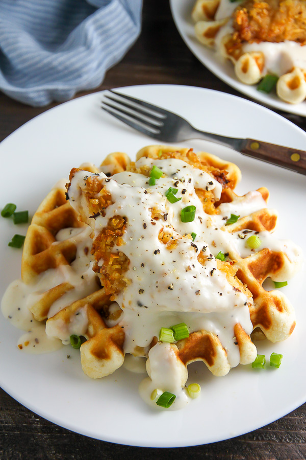 """Fluffy buttermilk waffles topped with crispy """"oven-fried"""" chicken and creamy white pepper gravy. Brunch perfection."""