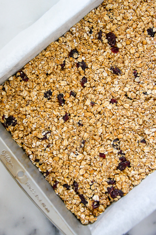 Loaded with cranberries, macadamia nuts, and topped with a sweet drizzle of white chocolate. These homemade granola bars are as easy as they are irresistible!