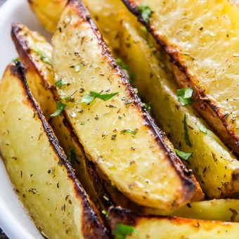 Extra crispy oven baked potato wedges flavored with garlic and herbs. Bet you can't eat just one!