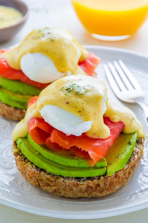 Smoked Salmon and Avocado Eggs Benedict on a white plate.