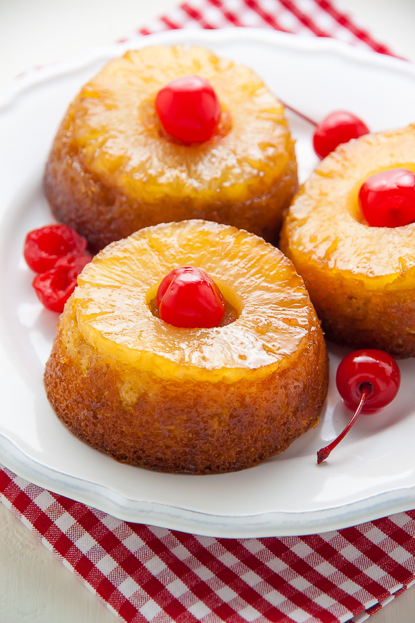 Individual pineapple upside-down cakes on white plate with checkered napkin.