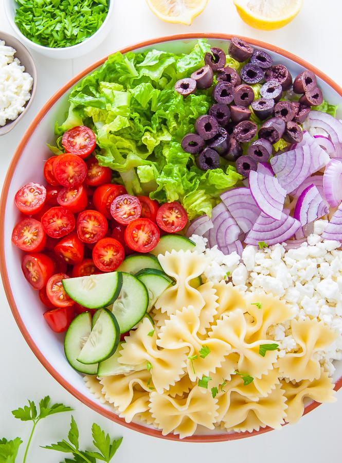 Ingredients for Greek Pasta Salad in serving bowl.