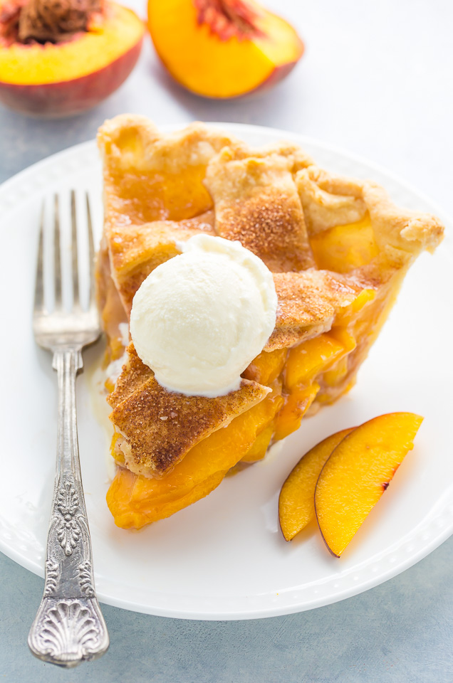 A slice of brown sugar cinnamon peach pie with ice cream on top.