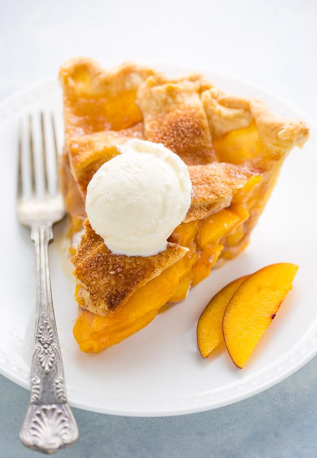 Slice of peach pie with vanilla ice cream on top.