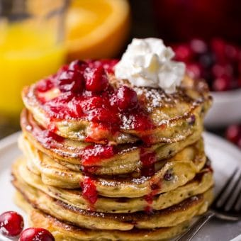 Fluffy and flavorful Cranberry Orange Pancakes are topped with Maple Cranberry Syrup!