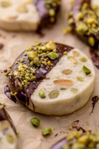 Dark Chocolate Pistachio Slice & Bake Cookies are so easy and made with just 6 ingredients! These buttery shortbread cookies are loaded with pistachios and then dunked in dark chocolate. So good with a cup of coffee or tea!
