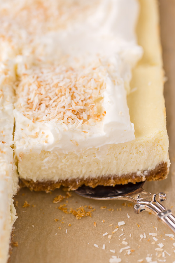 These Coconut Cheesecake Bars are creamy, sweet, and loaded with real coconut in every bite! Baked in cake pan and no water bath required, this recipe is easy and delicious! This family friendly recipe is always a crowd pleaser.