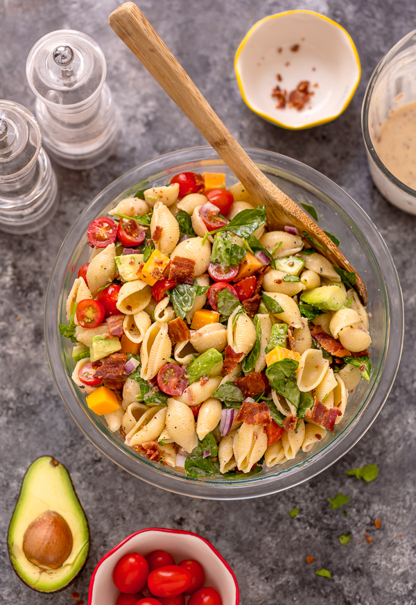 This Creamy Avocado BLT Pasta Salad is so easy and perfect for Summer celebrations! Loaded with crispy bacon, juicy tomatoes, spinach, avocado, and cheddar cheese. This flavorful pasta salad is always a crowd-pleaser!