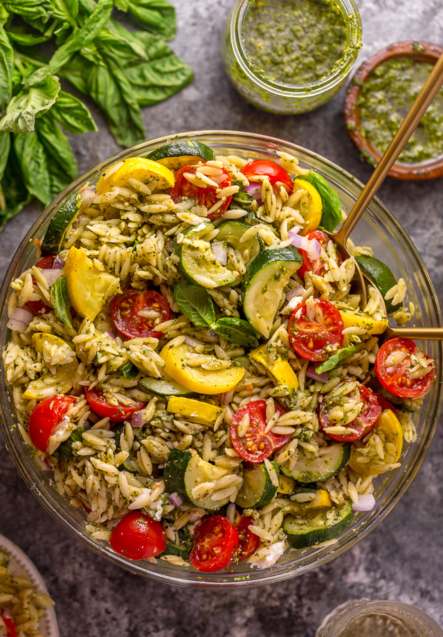 It's beginning to feel a lot like Summer, and you know what that means, right? It's PASTA SALAD SEASON! And this Pesto Orzo Pasta Salad with Zucchini, Goat Cheese, and Tomatoes is sure to be on heavy rotation all Summer long! This mayo-free pasta salad is vegetarian friendly and perfect for picnics, potlucks, and barbecues! #pestopastasalad #pesto #orzo #orzopastasalad