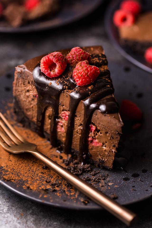 This Dark Chocolate Raspberry Cheesecake is pure decadence! It's not too sweet and but very rich, so a small slice goes far! The fresh raspberry pockets swirled throughout are delightfully refreshing! #chocolateraspberrycheesecake #chocolate #raspberry #raspberrycheesecake #cheesecake #Chocolatecheesecake #dessertrecipes