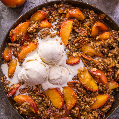 In my humble opinion, the only thing better than peach crisp is BOURBON PECAN PEACH CRISP! Made with brown sugar, fresh peaches, bourbon, and a touch of cinnamon, this is Summer in a baking dish! Serve warm while the fruit is bubbling, with a big scoop of vanilla ice cream on top! #peachcrisp #bourbonpecan #bourbonpeachpie #peaches #peachrecipes