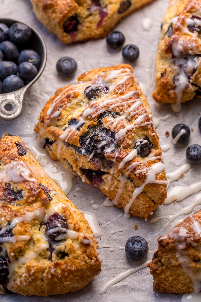These Classic Bakery-Style Blueberry Scones are sweet, buttery, and exploding with fresh blueberries! Topped with sparkling coarse sugar and a sweet vanilla glaze, these are perfect for breakfast or brunch! Even scone haters love this recipe!