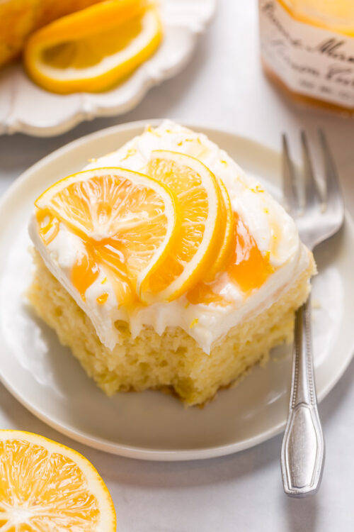 My lemon cake for a crowd is moist, fluffy, and loaded with fresh lemon flavor! Topped with silky smooth lemon cream cheese frosting, dollops of lemon curd, and fresh lemon slices, this is one of my most popular lemon desserts. Bonus: this lemon sheet cake is so easy and feeds a crowd!