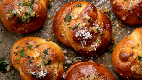 Soft Pretzel Garlic Knots are chewy, flavorful, and so delicious! Made with a simple soft pretzel dough, they're shaped like knots and baked until golden brown. Then topped with garlic butter and parmesan cheese!