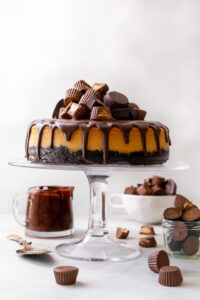 This Chocolate Covered Peanut Butter Cheesecake is ultra creamy and the perfect marriage of chocolate and peanut butter! Featuring an oreo crust, creamy peanut butter cheesecake filling, and topped with with peanut butter chocolate ganache and peanut butter cups, it's a true showstopper! And any leftovers freeze great!