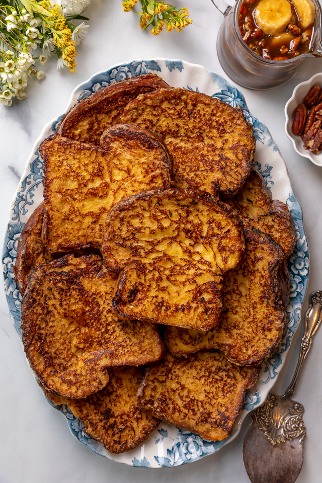 This Easy Bananas Foster French Toast is one of our favorite breakfast recipes! Crispy slices of buttery brioche are topped with a delicious homemade bananas foster sauce made from dark rum, butter, brown sugar, heavy cream, and crunchy pecans. Delicious on it's on, but devilishly good with whipped cream or vanilla ice cream!