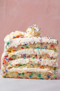 Featuring light and fluffy cake layers that are exploding with rainbow sprinkles and slathered in a silky smooth cream cheese buttercream frosting, this is the Ultimate Funfetti Birthday Cake Recipe!!! Perfect for any special celebration or birthday party! This cake is sure to bring a smile to your face!