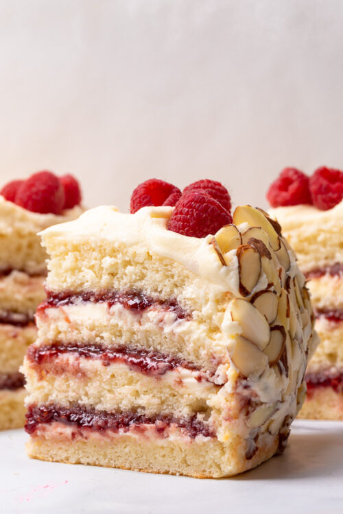 This Almond Raspberry Cake with White Chocolate Amaretto Buttercream Frosting is a total showstopper! Featuring four layers of light and fluffy almond cake, raspberry filling, and creamy white chocolate amaretto cream, this cake is decadently sweet! A must try if you love raspberry almond desserts!