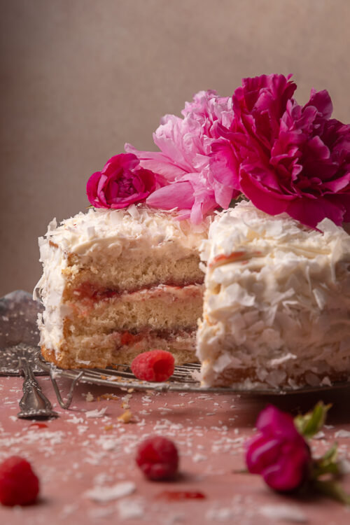 This ultra moist coconut cake is layered with raspberry filling and creamy coconut cream cheese frosting, and then coated in a thick layer of shredded coconut! Make it a showstopper by decorating with edible flowers or fresh raspberries. A must try for raspberry coconut lovers!
