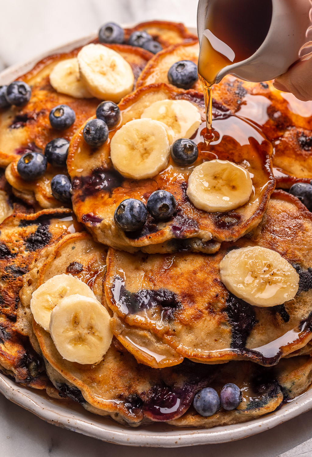 Ripe bananas and fresh blueberries make these Banana Blueberry Pancakes tender, fluffy, and flavorful! The pancake batter comes together in just minutes, and is quickly cooked to golden brown on a hot skillet. Top with maple syrup, extra blueberries, and banana slices for a beautiful breakfast at home!