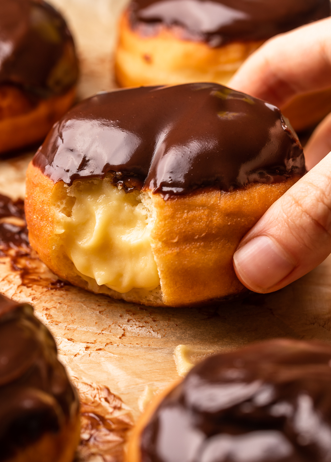 Fluffy Boston Cream Donuts are stuffed with pastry cream filling and dipped in a rich chocolate glaze! Don't let the deep frying scare you off, because this recipe is worth every step. And so much better than anything you'll get from the donut shop.